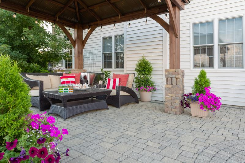Brussel block design pavers on an exterior patio. And summer living space with a covered gazebo, colorful petunias and comfortable seating stock photo