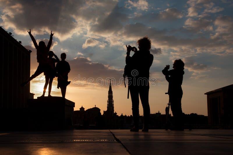 Brussel - Silhouet van gesprongen jongens over de stad op Monts des Arts in avond stock afbeeldingen