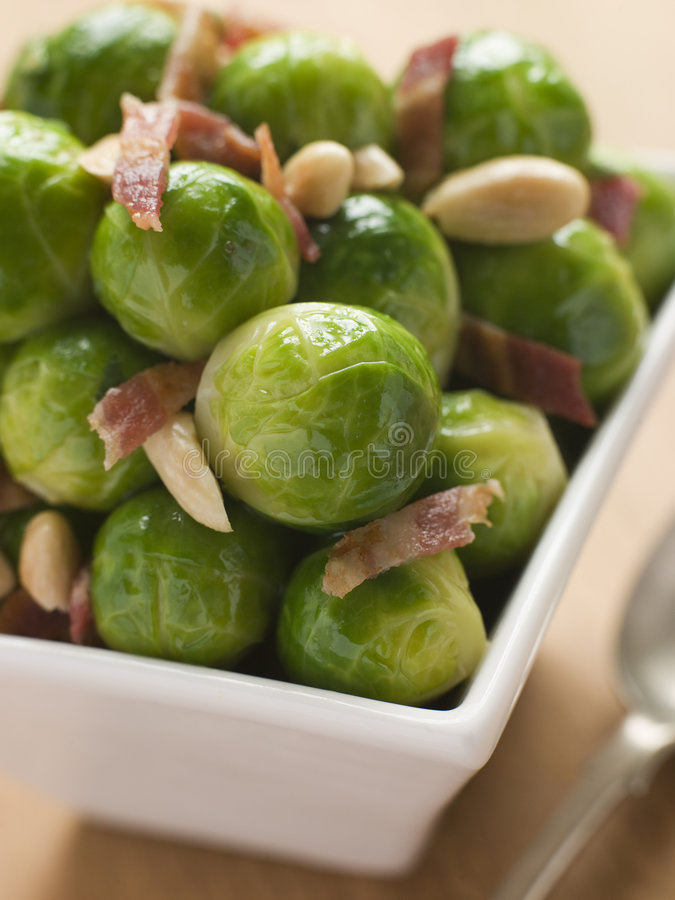 Brussel Sprouts with Fried Bacon and Almonds. Close up Brussel Sprouts with Fried Bacon and Almonds in Bowl stock images