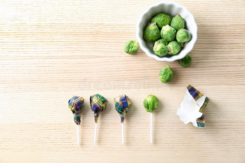 Brussel sprouts with lollipop sticks. In candy wrappers on table. April fools food royalty free stock photos