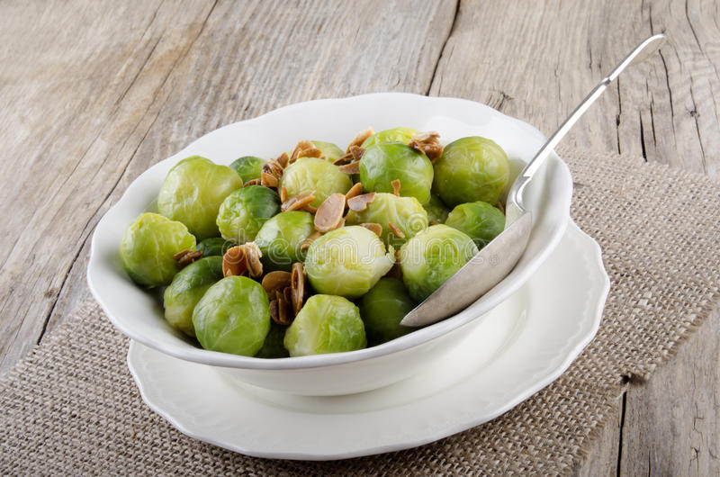 Brussel sprouts with roasted almonds in a bowl. Brussel sprouts with roasted almonds in a white bowl stock photo