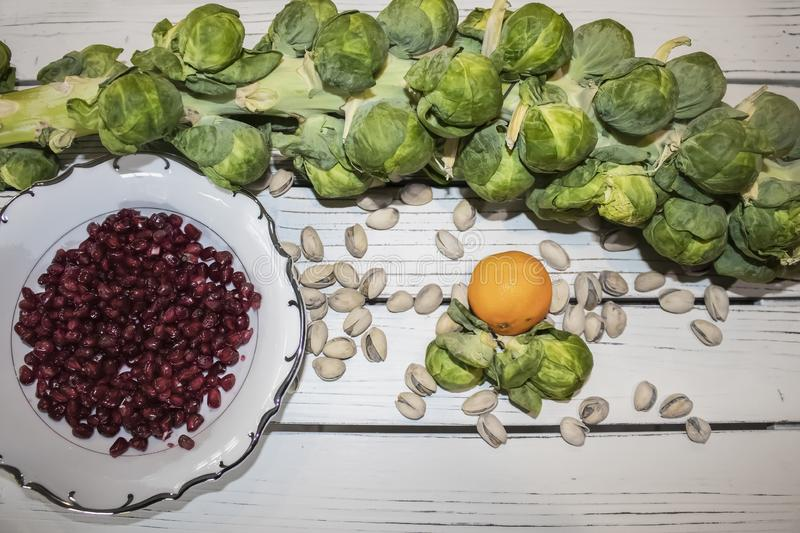 Brussel sprouts on a stalk with a plate of pomegranate seeds and pistachio nuts and a small orange scattered around on a white stock photos