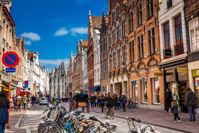 People touring around the beautiful Bruges town on a carriage pulled by a horse. BRUSSELS, BELGIUM - MARCH, 2018:People touring around the beautiful Bruges town stock images