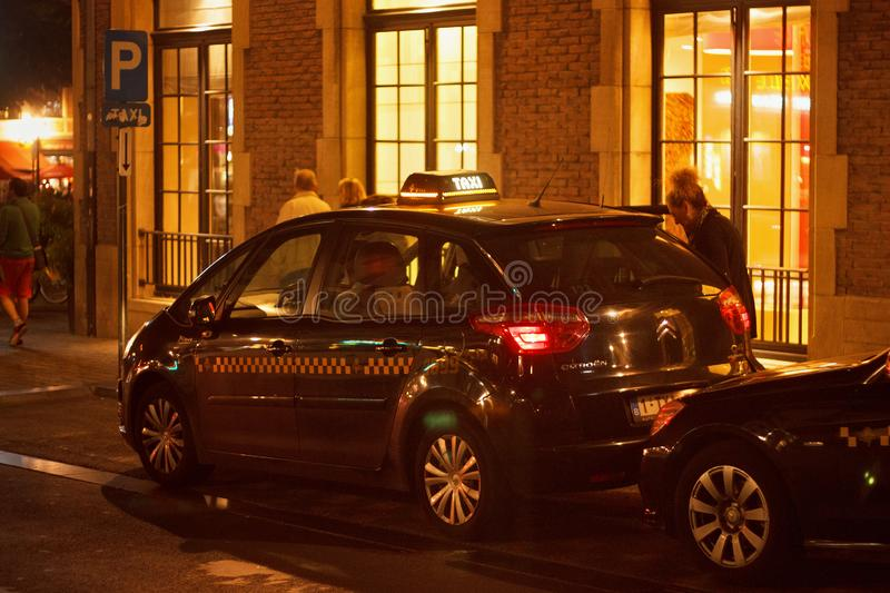 BRUSSELS, BELGIUM - SEPTEMBER 06, 2014: Black taxi car near roadside in the historic part of Brussels. royalty free stock image