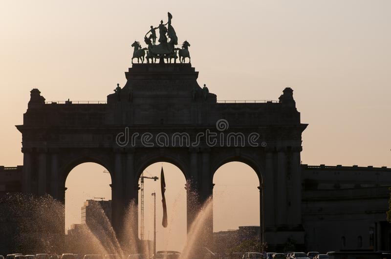 Brussels, Belgium, Triumphal Arch,Jubilee Park, Parc du Cinquantenaire with fountain in front at sunset. royalty free stock photography