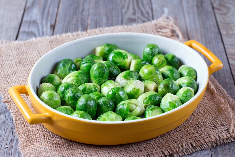 Brussels sprouts in baking dish. On a wooden background royalty free stock photography