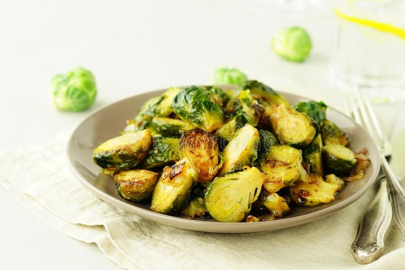 Brussels sprouts roasted fried with onions on a plate top view. stock images