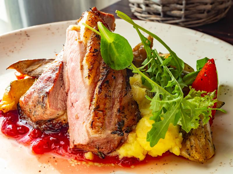 Brust der gebratenen Ente mit Gemüsegarnierung Das Fleisch wird in Teile geschnitten und besprüht mit Moosbeerbeerensoße lizenzfreies stockbild