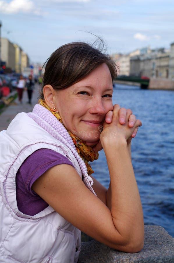 Brustbild der modischen jungen Frau, die nahe dem Fluss beim Genießen des Schlenderns am warmen Frühlingstag, schön und am gorg s stockfotos