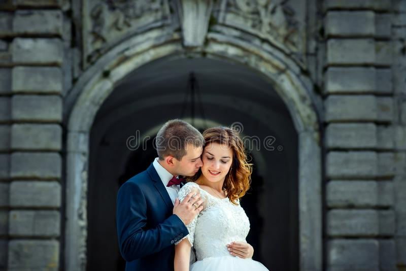 Brustbild des Bräutigams, der leicht die lächelnde Brauthauptrückseite des Ingwers umarmt stockfotos