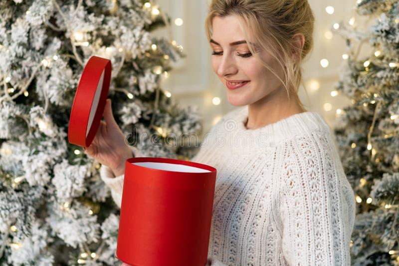 Brustbild des jungen schönen blonden Mädchens öffnet das Geschenk mit Interesse lizenzfreies stockfoto