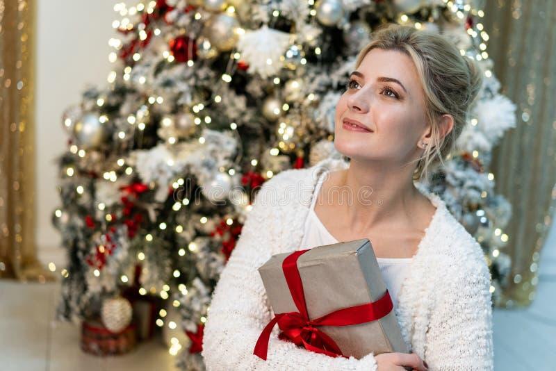 Brustbild des schönen jungen blonden Mädchens in der weißen Strickjacke, die mit Geschenk nahe dem Weihnachtsbaum aufwirft lizenzfreie stockfotos