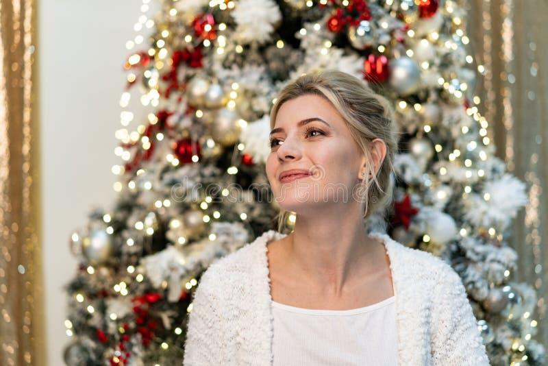 Brustbild des schönen jungen blonden Mädchens in der weißen Strickjacke, die nahe dem Weihnachtsbaum aufwirft lizenzfreies stockbild