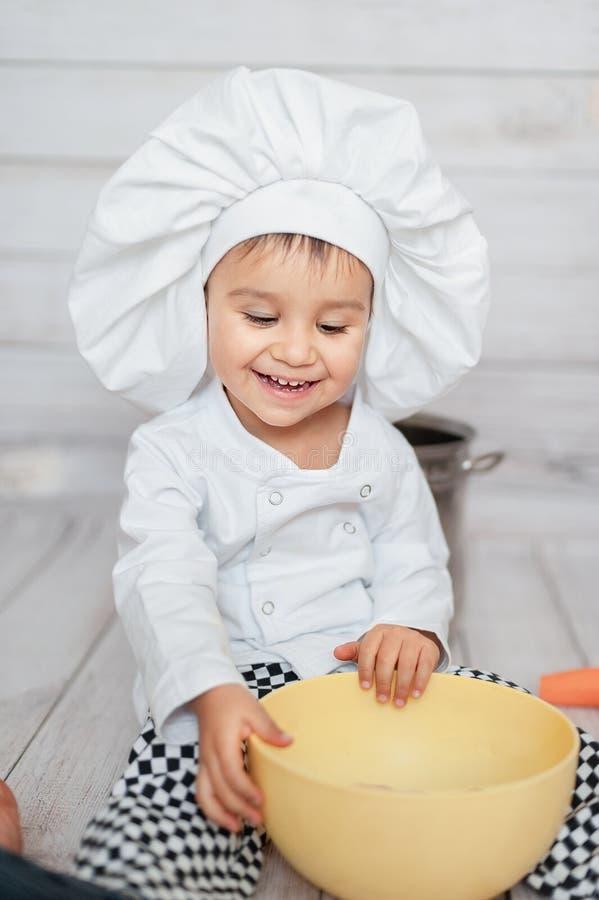 Brustbild eines kleinen Chefs Nettes kleines Kind im Schutzblech- und Chefhut betrachtet Kamera stockfoto