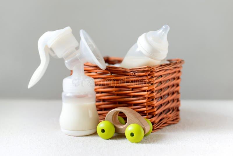 Brustpumpe und Babyflasche mit Muttermilch für Baby in einem Strohkorb Freiexemplarraum lizenzfreie stockbilder
