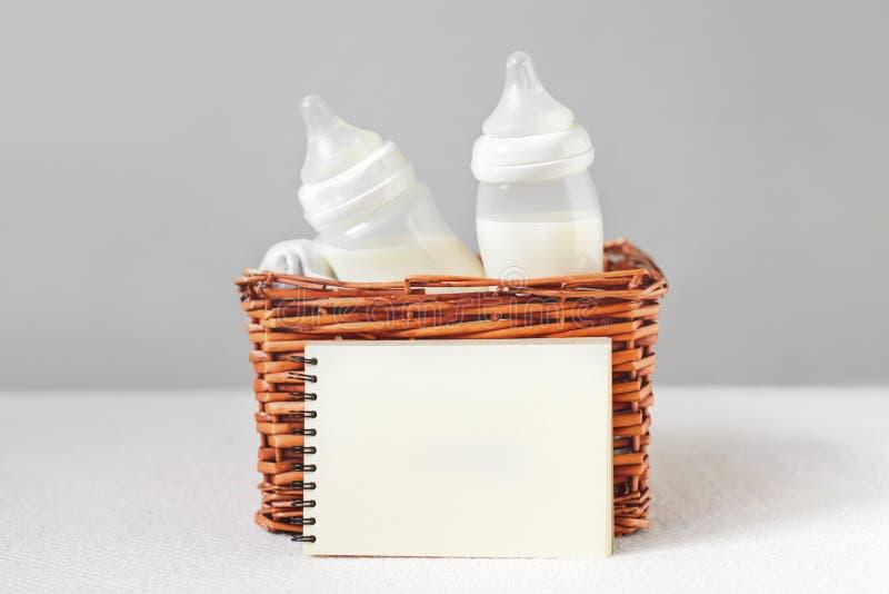 Brustpumpe und -flasche mit Milch für Baby in einem Strohkorb- und -papiernotizbuch nahe ihm Freiexemplarraum lizenzfreie stockfotos