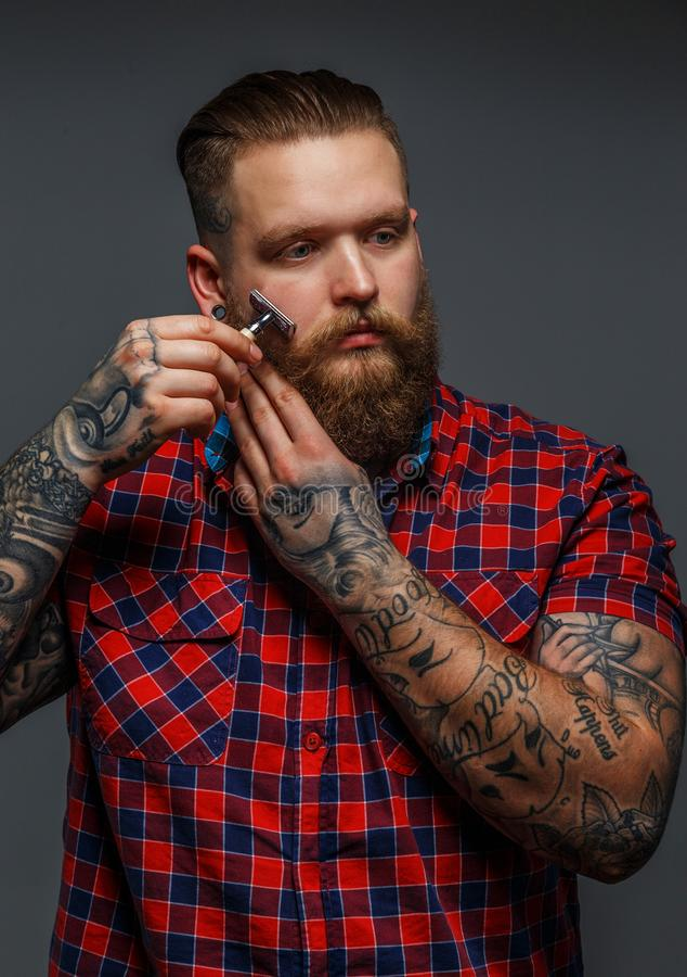 Brutaal getatoeeerd mannetje die zijn baard shawing stock afbeeldingen
