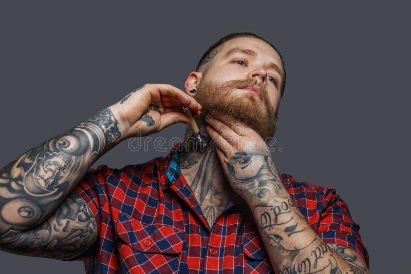 Brutaal getatoeeerd mannetje die zijn baard shawing stock afbeelding