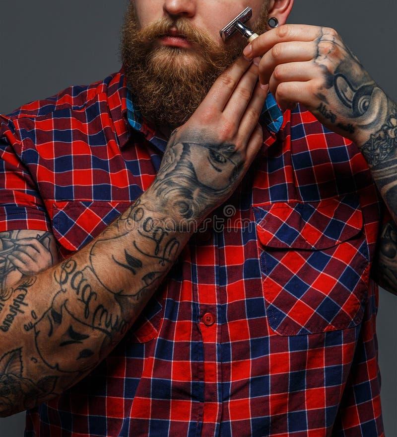 Brutaal getatoeeerd mannetje die zijn baard shawing royalty-vrije stock foto