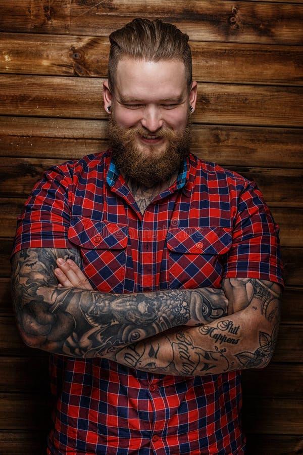 Brutaal reusachtig mannetje met baard en tatoegeringen met glimlach op zijn gezicht stock afbeelding