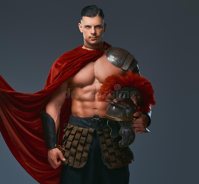 Brutal ancient Greece warrior with a muscular body in battle uniforms holds a helmet while standing in a studio. stock image