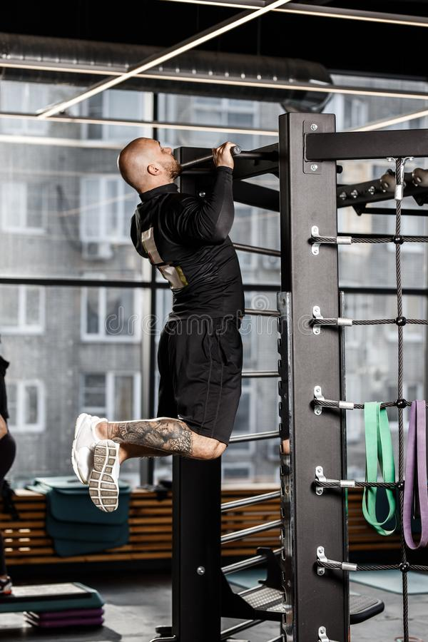 Brutal athletic man dressed in black sorts clothes pulls up on the bar in the gym royalty free stock image