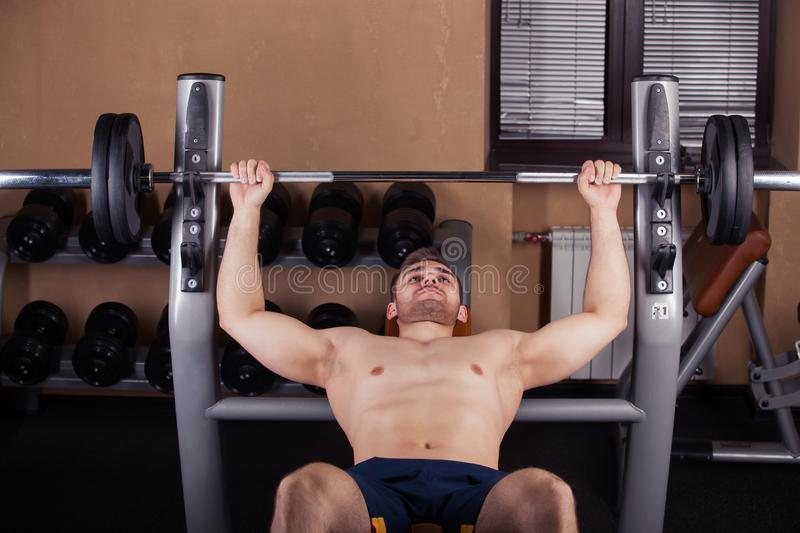 Brutal athletic man pumping up muscles on bench press royalty free stock photography