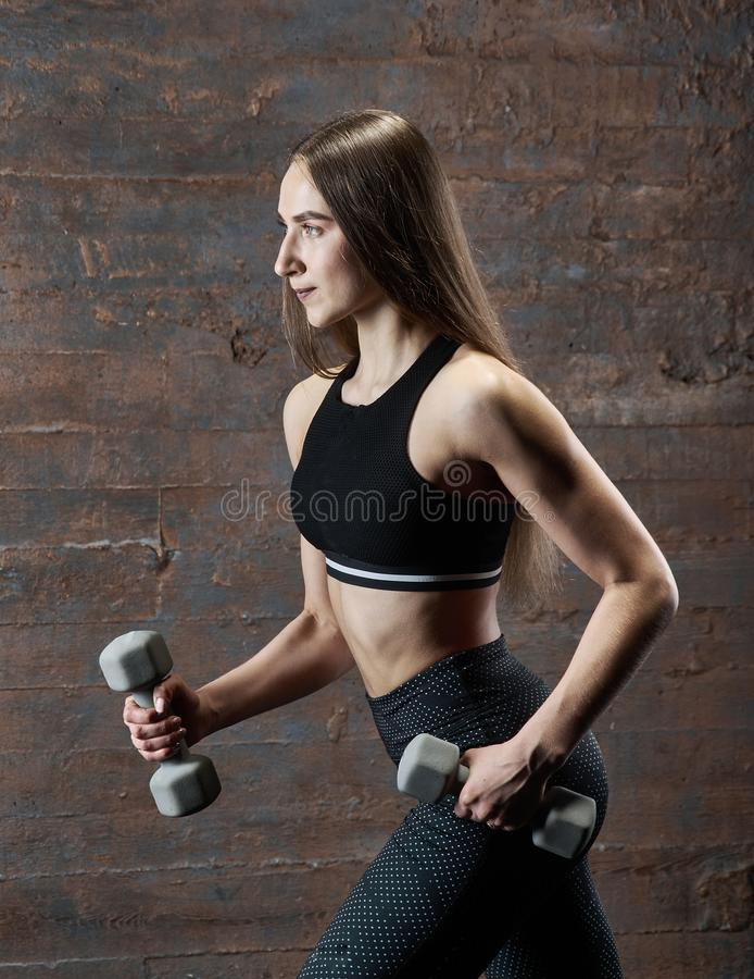 Brutal athletic woman pumping up muscles with dumbbells royalty free stock photos