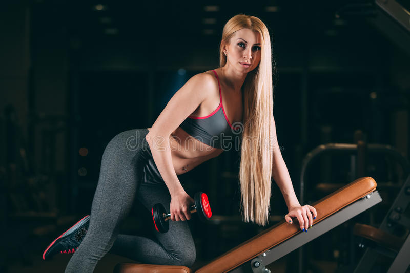 Brutal athletic woman pumping up muscles with dumbbells in gym stock image