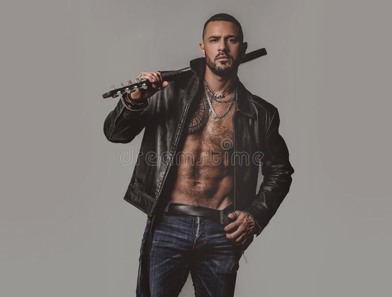 Brutal attractive bearded biker man with tattooed poses in black jacket. Copy space. Handsome bearded man. Serious. Stylish bearded man. Rock fan or gangster stock image
