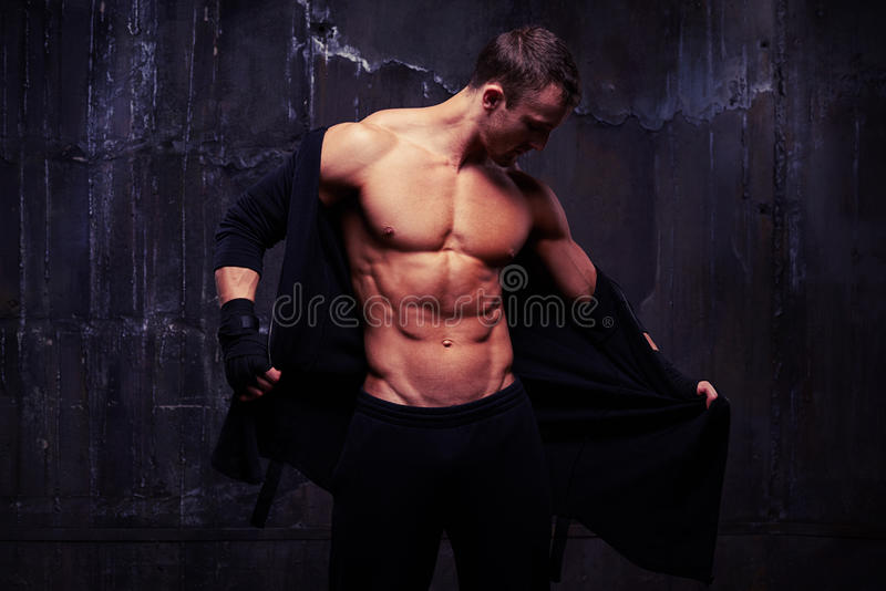 Brutal bare-chested muscular male taking off a black hoodie while standing over black background stock photos