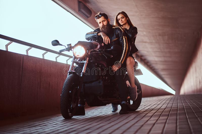 Brutal bearded biker in black leather jacket and sensual brunette girl sitting together on a custom-made retro stock photos