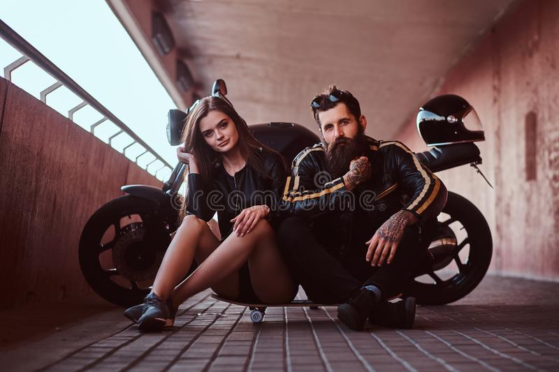 Brutal bearded biker in black leather jacket and sensual brunette girl sitting together on a skateboard near custom-made royalty free stock photos