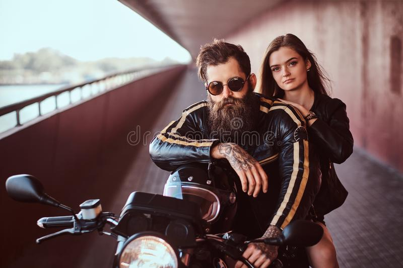 Brutal bearded biker in a black leather jacket with sunglasses and sensual brunette girl sitting together on a custom royalty free stock photo