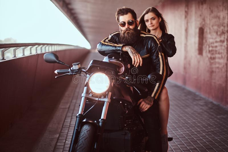 Brutal bearded biker in a black leather jacket with sunglasses and sensual brunette girl sitting together on a custom stock images