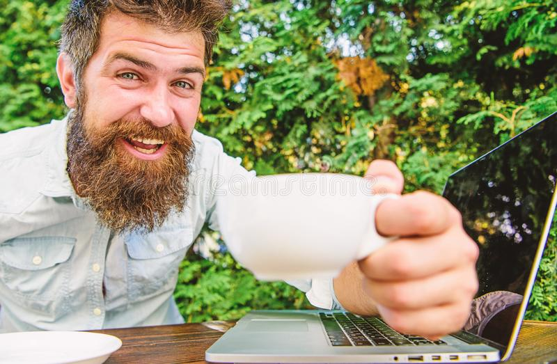 Brutal bearded hipster at coffee break. happy man working on laptop. perfect deal. office worker. Successful businessman stock photography