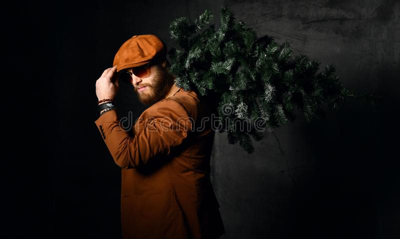 Brutal bearded man in brown leather jacket and cap hat aviator sunglasses hold Christmas tree stock photography