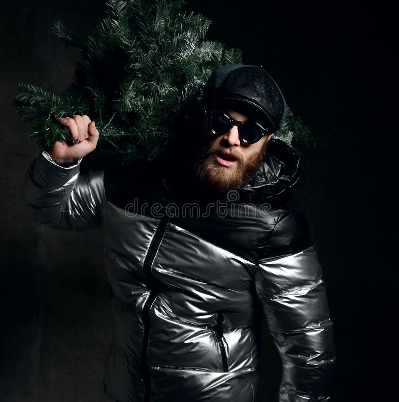 Brutal man in silver winter jacket, cap hat hold Christmas tree on dark stock images