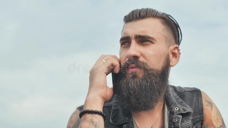 Brutal bearded man talking on the phone and smokes a cigarette. royalty free stock photo