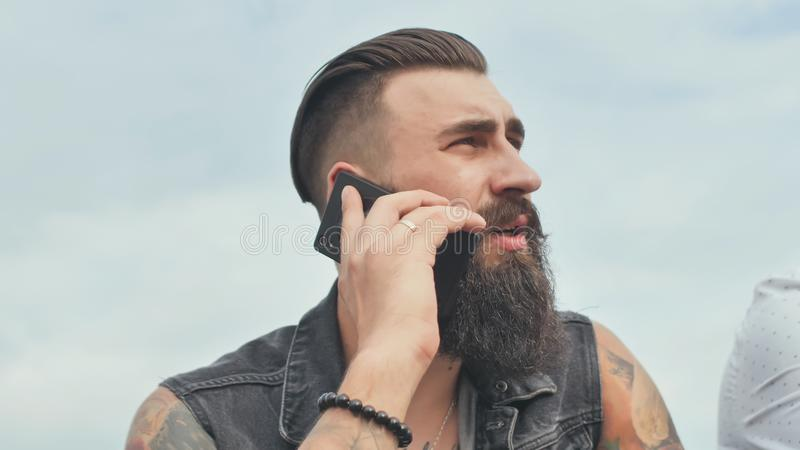 Brutal bearded man talking on the phone and smokes a cigarette. Brutal bearded man talking on the phone and smokes a cigarette royalty free stock photography