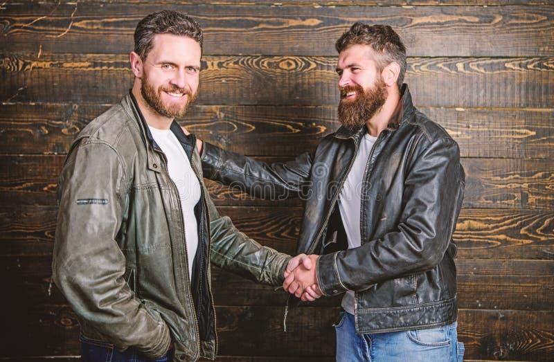 Brutal bearded men wear leather jackets shaking hands. Real men and brotherhood. Strong handshake. Friendship of brutal stock photography
