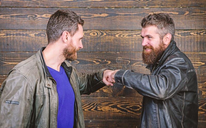 Brutal bearded men wear leather jackets shaking hands. Strong handshake. Friendship of brutal guys. Approved business stock image