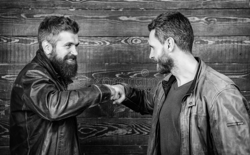 Brutal bearded men wear leather jackets shaking hands. Strong handshake. Friendship of brutal guys. Approved business royalty free stock photography