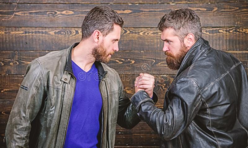 Brutal bearded men wear leather jackets shaking hands. Strong handshake. Friendship of brutal guys. Handshake symbol of stock photos