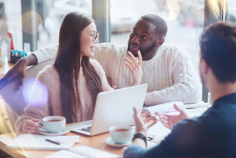 Brutal black-skinned bearded man listening to his colleague. Listen to me. Positive delighted young women keeping smile on her face and sitting in semi position royalty free stock image