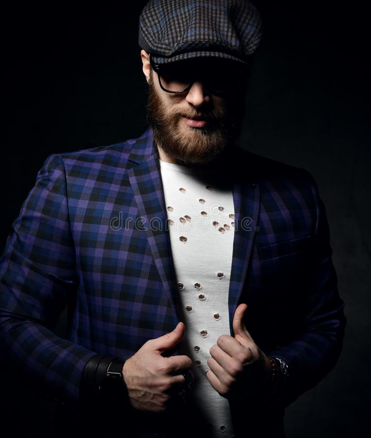 Brutal business man with beard mustache and glasses in fashion cap and blue square jacket royalty free stock images