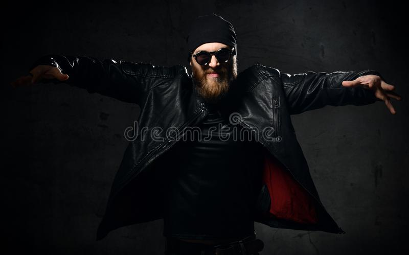Brutal business man gangster with beard and mustache in sunglasses cap and leather wear jacket with raised hands royalty free stock images