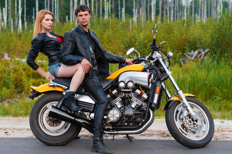 Brutal couple of bikers motorcyclists on motorcycle royalty free stock images
