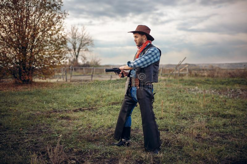 Brutal cowboy with revolver, gunfight on ranch. Brutal cowboy with revolver, gunfight on texas ranch, western. Vintage male person with gun, wild west lifestyle royalty free stock photography