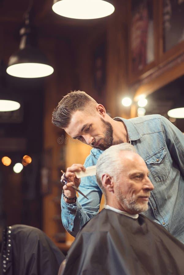 Brutal frisör som kammar frisyr av klienten i salongen royaltyfria foton